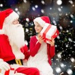Smiling little girl with santa claus and gifts — Stock Photo #57772173