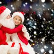 Smiling little girl with santa claus and gifts — Stock Photo #57772189