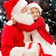 Smiling little girl with santa claus and gifts — Stock Photo #57772227