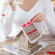 Close up of woman making gingerbread houses — Stock Photo #57772587
