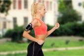 运行智能手机与耳机的运动型女人 — 图库照片