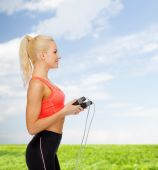 Smiling sporty woman with skipping rope — Stock fotografie