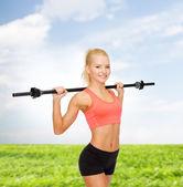 Usmívající se sportovní žena cvičení s činka — Stock fotografie