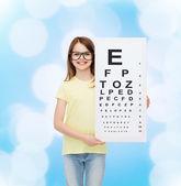 Little girl in eyeglasses with eye checking chart — Stock Photo