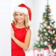 Smiling young woman in santa hat with white board — Stock Photo #57859851