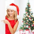 Smiling young woman in santa hat with white board — Stock Photo #57859969