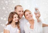 Happy family with camera taking picture at home — Stock Photo