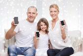 Glückliche Familie zeigen Smartphones leere Bildschirmen — Stockfoto