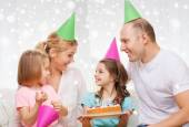Happy family with two kids in party hats at home — Stock Photo