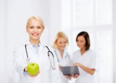 Smiling female doctor with green apple — Stock Photo