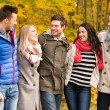 Group of smiling men and women in autumn park — Stock Photo #57864839
