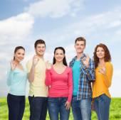 青い空と草に笑みを浮かべてティーンエイ ジャーのグループ — ストック写真