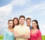 Группа улыбающихся подростков на голубое небо и трава — Стоковое фото