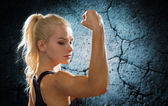 Sporty woman flexing and showing biceps from back — Stock Photo