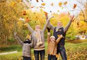 Happy family playing with autumn leaves in park — Stock Photo