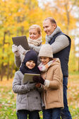 Happy family with tablet pc in autumn park — Stock Photo