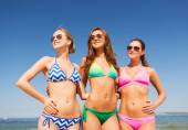 Group of smiling young women on beach — Stock fotografie