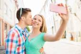 Lachende paar met smartphone in stad — Stockfoto