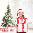 Girl in santa helper hat with many gift boxes — Stock Photo #57941695