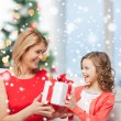 Smiling mother and daughter with gift box at home — Stock Photo #57941981