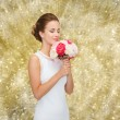 Smiling woman in white dress with bouquet of roses — Stock Photo #57947663