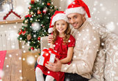 Smiling father and daughter with gift box at home — Stockfoto