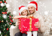 Smiling father and daughter with gift box at home — Stock Photo