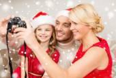 Happy family with digital camera taking photo — Stockfoto