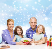 Happy family with two kids showing salad in bowl — Stock Photo