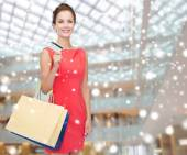 Smiling woman with shopping bags and plastic card — Stock Photo