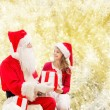 Smiling little girl with santa claus and gifts — Stock Photo #57953083