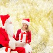 Smiling little girl with santa claus and gifts — Stock Photo #57953111