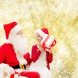 Smiling little girl with santa claus and gifts — Stock Photo #57953161