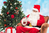 Santa claus with smartphone and christmas tree — Stok fotoğraf