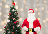 Man in costume of santa claus with christmas tree — Stock Photo