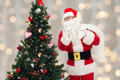 Santa claus with bag and christmas tree — Photo