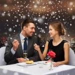 Smiling couple eating dessert at restaurant — Stock Photo #58109563