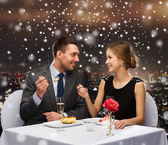 Smiling couple eating dessert at restaurant — Stock Photo