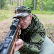 Close up of soldier or hunter with gun in forest — Stock Photo #58118435