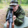 Close up of soldier or hunter with gun in forest — Stock Photo #58118449
