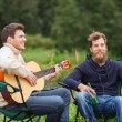 Smiling tourists playing guitar in camping — Stock Photo #58118617