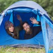 Smiling couple of tourists looking out from tent — Stock Photo #58118713