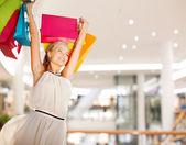 買い物袋を持つ若い女性の笑みを浮かべてください。 — ストック写真
