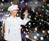 Smiling female chef writing something on air — Stock Photo