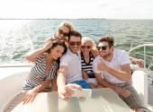 Улыбающиеся друзей, сидя на палубе яхты — Стоковое фото