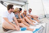 Smiling friends sitting on yacht deck — ストック写真