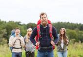 Group of smiling friends with backpacks hiking — Stock Photo