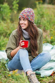 Smiling young woman with cup sitting in camping — Photo