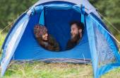 Smiling couple of tourists looking out from tent — ストック写真