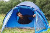 Smiling male tourist with beard in tent — Photo